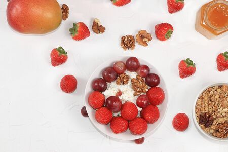 Strawberry yogurt, granola, cottage cheese, fresh berries, mangoes, strawberries and grapes on a light table. The concept of healthy and natural food. Useful breakfast, food for children, selective focus, top view Foto de archivo
