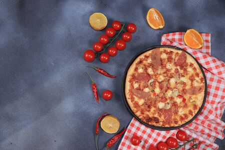 Pizza with ham, tomatoes, lemon and cheese on a dark old background., Selective focus. The concept of a modern bakery, top view,