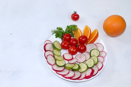 Vegetable salad on a light table, the concept of detox diet, healthy and natural food. Radishes, cucumbers, tomatoes and lemon contribute to improving metabolism and losing weight. Flat lay,