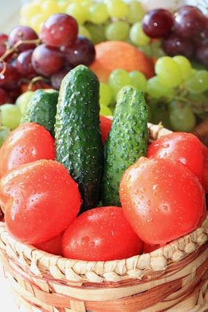 Tomatoes and cucumbers with drops in a basket. The concept of healthy and natural foods to enhance immunity, healthy lifestyles, vitamins, detox diet. Selective focus, close-up. Stockfoto