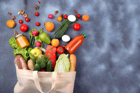 Healthy natural food in an eco bag, concept of a healthy lifestyle, zero waste. Food delivery, donation, quarantine of coronavirus. Vegetables, fruits and fish in tissue packaging, Stock Photo