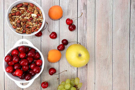 Healthy breakfast with ingredients, summer fruits and berries with granola, grapes, cherries and peaches on a bright table. The concept of a healthy and natural diet, lifestyle,