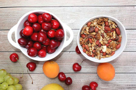 Healthy breakfast with ingredients, food for children, summer fruits and berries with granola, grapes, cherries and peaches on a bright table. The concept of a healthy and natural diet, lifestyle, Stock Photo