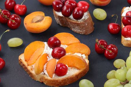 Diet fruit toasts with cottage cheese, peaches, grapes and cherries, healthy breakfast with ingredients. The concept of healthy and natural food, lifestyle, flat lay,