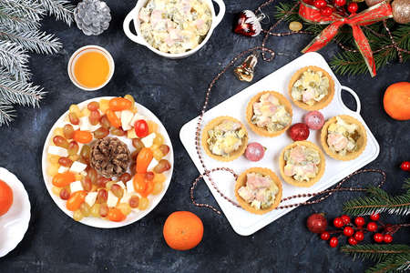 Christmas new year dishes, traditional festive salad olivier and cheese with tomatoes, grapes and honey with fir branches and cones and decorations, dish design idea,