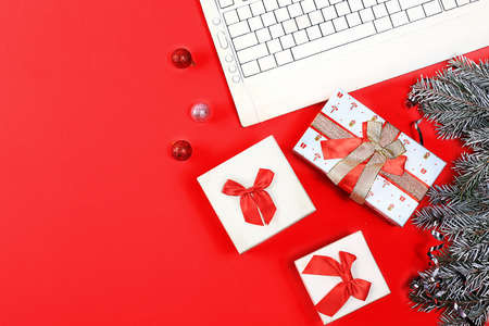 Online shopping gift concept, sale, gift boxes and computer on red background, christmas background, place for text, banner, postcard, festive atmosphere,