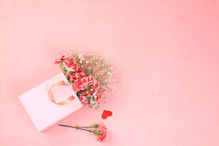 Carnations in a pink box, abstract spring floral background. Creative modern bouquet, minimal holiday concept. Postcard for womens day or mothers day, happy birthday, wedding, banner for the screen,