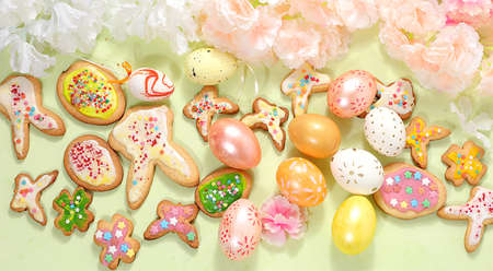 Festive Easter background, spring card, composition with flowers, cookies and eggs on a gentle background. Festive minimal concept, home baking ideas, place for text, banner for screen, selective focus