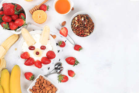 Useful breakfast of ingredients, strawberry yogurt with muesli, grapes, banana and honey on a bright table, fruit salad. Healthy and natural food concept, lifestyle, food for children, selective focus