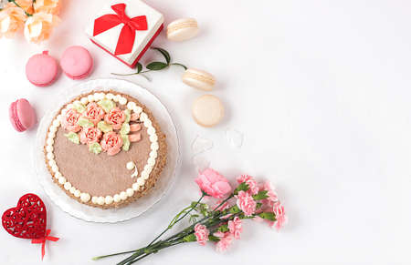 Cake with chocolate and meringue, marshmallows and flowers on a light table, festive food for mother's day, wedding, birthday. Modern bakery concept, selective focus, delicious dessert.