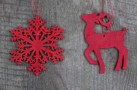 toys pattern: Wooden red christmas deer and snowflakes on wooden background.  Top view. Stock Photo