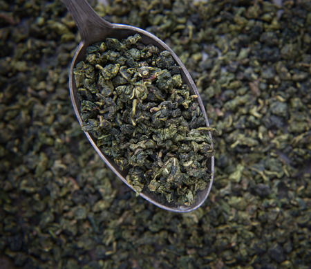 focus on background: Green tea on metal spoon Stock Photo