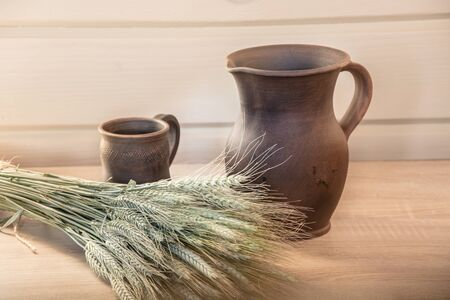 wheat kernel: Clay jug and a cup on the table with a bouquet of wheat