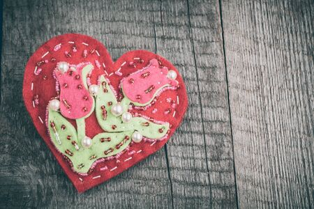 felicitaciones cumplea�os: Red handmade heart on wooden table background with copy space.  Valentines day. Matte and toned. Soft focus. Foto de archivo