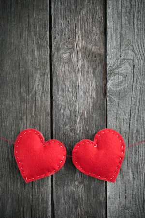 nicely: Two red hearts placed nicely on vintage wood background Stock Photo