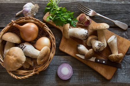Fresh white mushrooms with parsley in basket. Ingredients for mushroom's cream-soup on a rustic wooden board, overhead view. Standard-Bild
