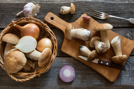 overhead view: Fresh white mushrooms in basket and ingredients for mushrooms cream-soup on a rustic wooden board, overhead view.