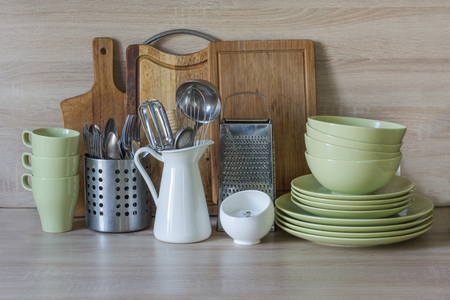 metal grater: Kitchen still life as background for design. Crockery, tableware and other different stuff on wooden table-top. Image with copy space.