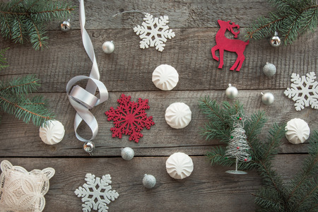 pastila: Christmas decor laid out on a wooden surface. Fir branches, silver ribbon and ball, white marshmallow, snowflakes, toy red deer and decor around. Top view and copyspace. Flat lay.
