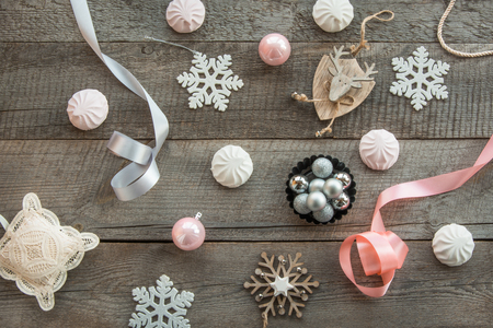 pastila: Christmas decor laid out on a wooden surface. Fir branches, pinksilver ribbon and ball, white marshmallow, snowflakes, toy deer and decor around. Top view and copyspace. Flat lay. Shabby-chic