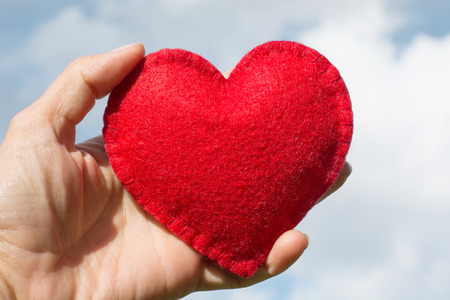 Red felt heart shape in the hand on the blue sky with clouds as background. Greeting card for Valentines Day.