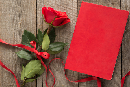 note booklet: Valentines card. Red rose and red notebook on wooden board. Top view.
