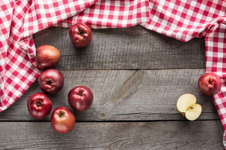 Ripe red apples on wooden board with red checkered napkin around and copy space. Stock Photo