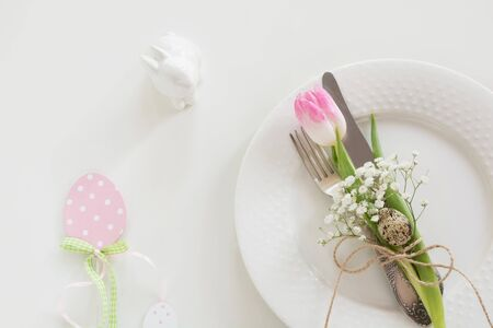 Easter table setting with pink ribbon and tulip on white background. Spring romantic dinner. Top view and copy space for your text.