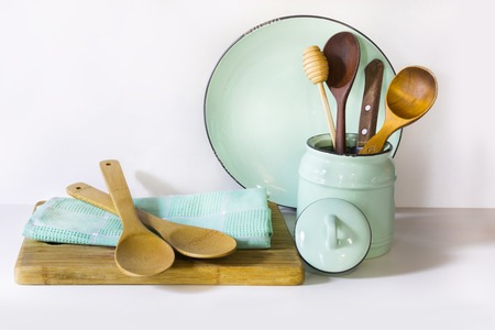 enamel: Crockery, tableware, utensils and other different white and turquoise stuff on white table-top. Kitchen still life as background for design.  Image with copy space.
