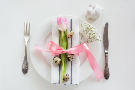 huevos de codorniz: Elegance table setting with pink ribbon and tulip on white background. Easter romantic dinner. Top view. Foto de archivo