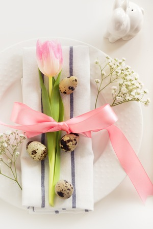 Elegance table setting with pink ribbon and tulip on white background. Easter romantic dinner. Top view. Stock Photo