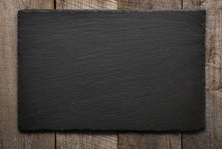 Black slate tile on wooden background .