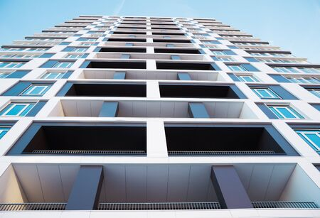Modern and new apartment building. Photo of a tall block of flats with balconies in Moscow against a blue sky.