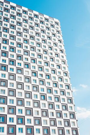 Modern and new apartment building. Photo of a tall block of flats against a blue sky.