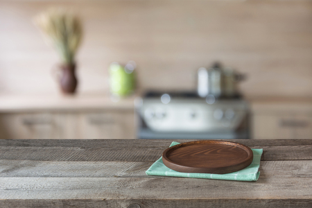 kitchen furniture: Blurred and abstract background. Empty wooden tabletop with tray and defocused modern kitchen background for display or montage your products. Stock Photo