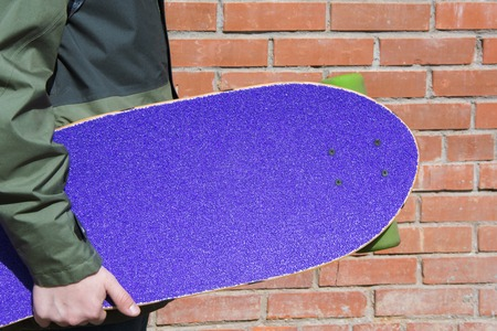 Teen hold purple longboard near the brick wall. Shallow depth of field. Close up. 版權商用圖片