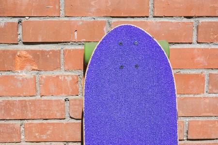 Purple longboard on the brick wall. Shallow depth of field. Close up.