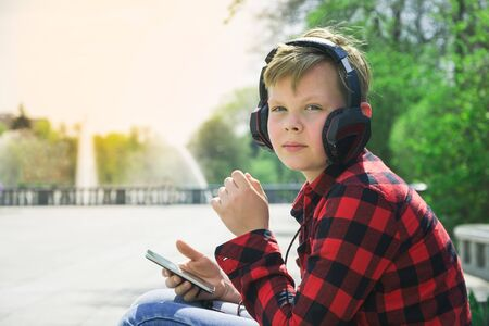 smarthone: Handsome teenager surfing the net while sitting on a longboard and listening to music.