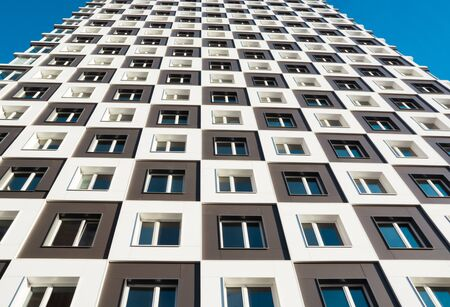 magnificence: From below shot of modern and new apartment building. Photo of a tall block of flats against a blue sky.