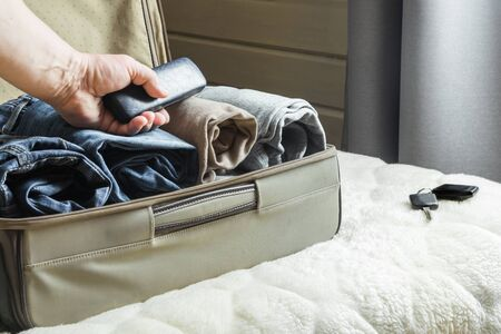 A man handles things. Open suitcase with clothes on the bed. View to the bedroom. Stock Photo