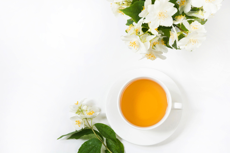 Jasmine flowers and cup of green tea on white. Top view and concept. Stockfoto