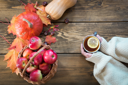 Cup of warming tea with lemon in hand and harvest, pumpkin, apples, colorful autumn leaves on wooden board. Top view.