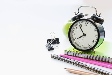 Colorful school supplies, book and alarm clock on white background. Close up. Back to school.