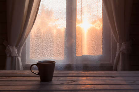 Cup of black coffee in front of the window on the wooden background. Copy space. Romance sunset.