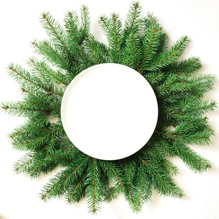 tradition: Creative layout made of christmas tree branches with empty plate on white background. Top view. Christmas concept.