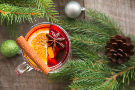 Mulled wine with cinnamon and christmas tree, decor on board. Top view.