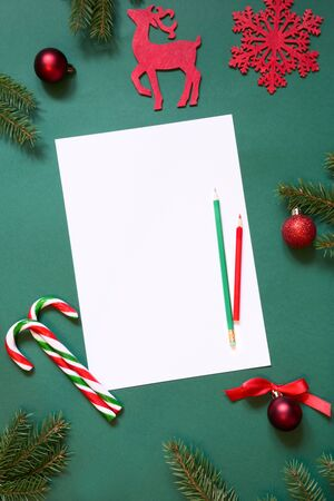 Christmas white blank for letter to Santa or your invitation or advent activities on green background. Top view. Flat lay. Standard-Bild