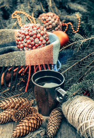 Cup of hot tea on a rustic wooden table. Still life of cones, twine, fir branches. Preparing for Christmas.  Vintage toned.