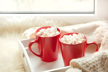 Two red cup of hot chocolate with marshmallow on white windowsill with furskin for rest. Holiday concept. Home style. Stock Photo