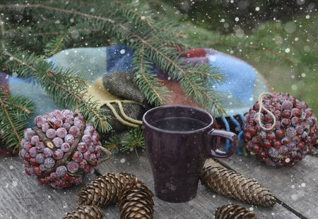 Ð¡up of hot tea on a rustic wooden table. Still life of cones, twine, patskthread, fir branches. Preparing for Christmas. Stock Photo
